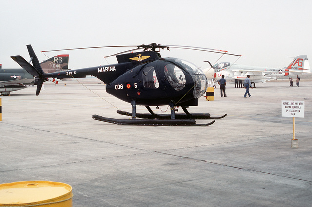 A right side view of a Spanish navy Hughes Model 500 helicopter parked on the flight line