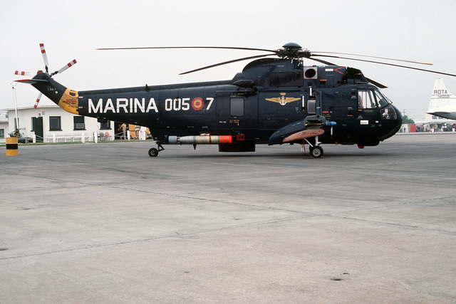 A right side view of a Spanish navy SH-3D Sea King helicopter parked on the flight line