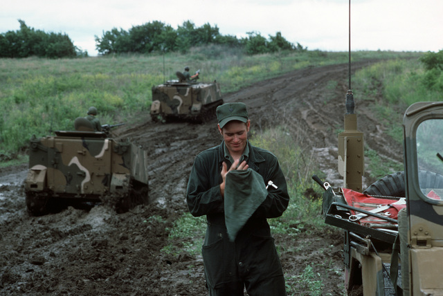 A US Army maintenance technician cleans his hands after servicing a vehicle during a field training exercise. In the background two M113 armored personnel carriers travel through a muddy section of road