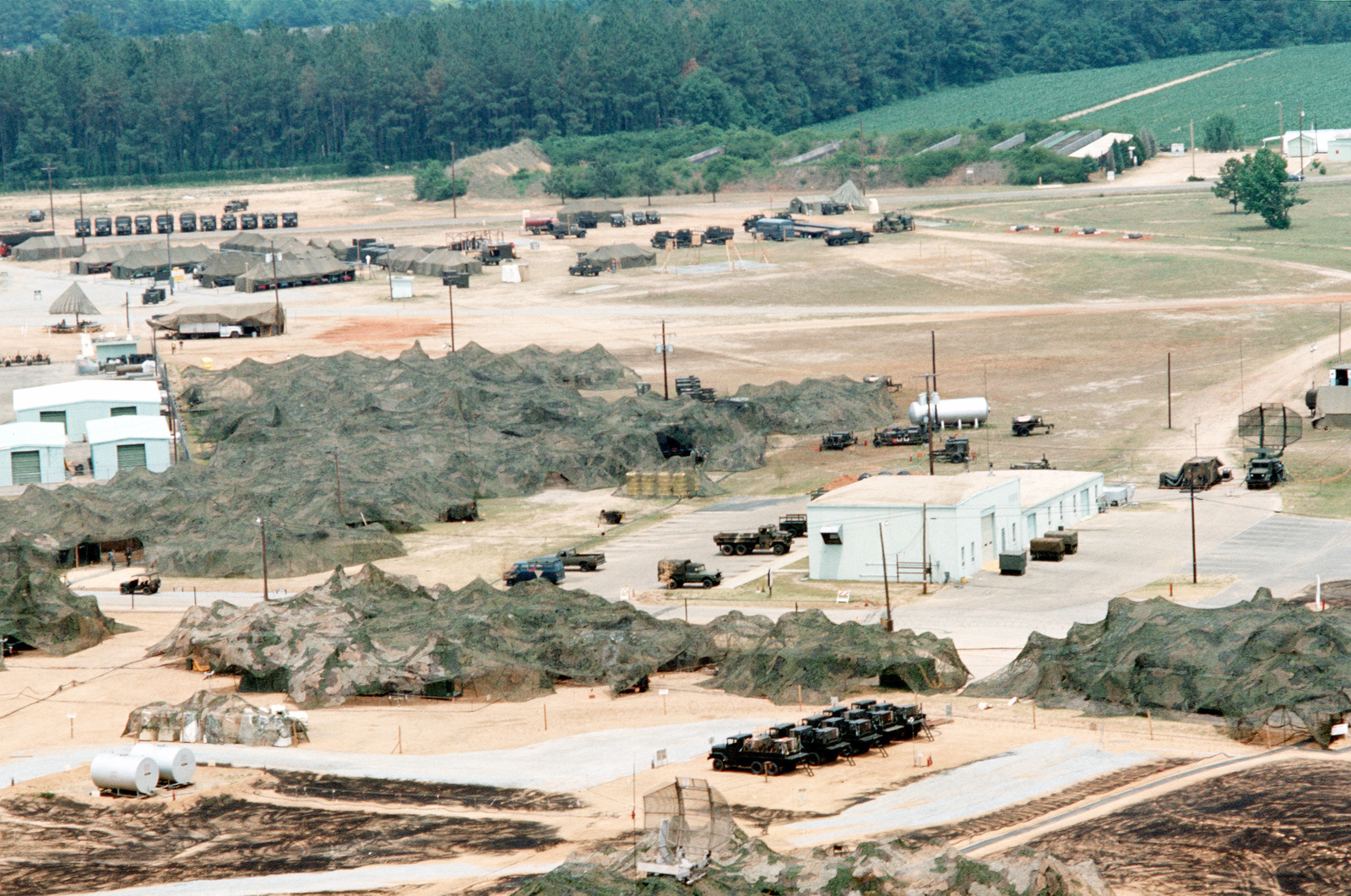 An aerial view of a camouflaged AN/TPS-43 tactical 3-D radar installation in use during joint readiness training exercise SOLID SHIELD '77