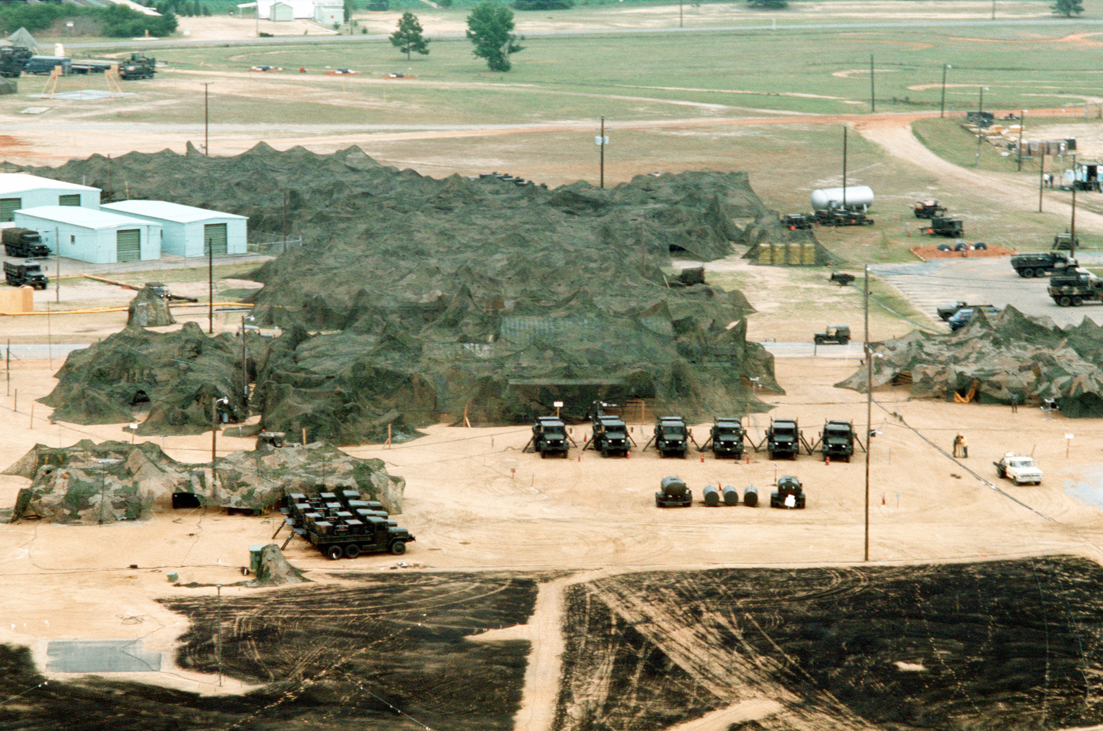An aerial view of a camouflaged tent complex in use during joint readiness training exercise SOLID SHIELD '77