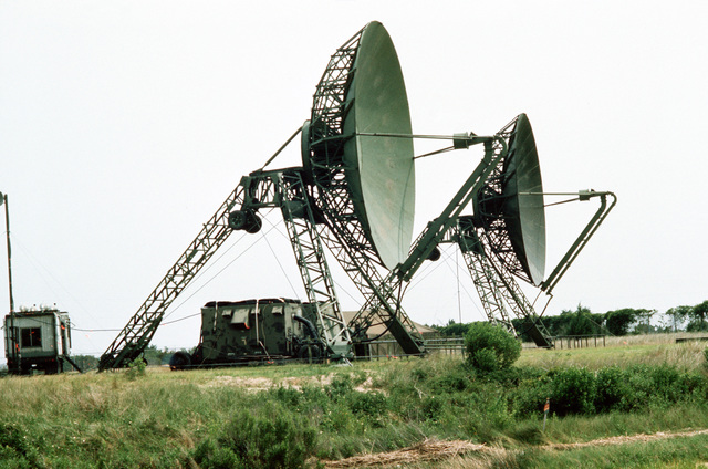 Two large dish-shaped radar antennas in use during joint readiness training exercise SOLID SHIELD '77