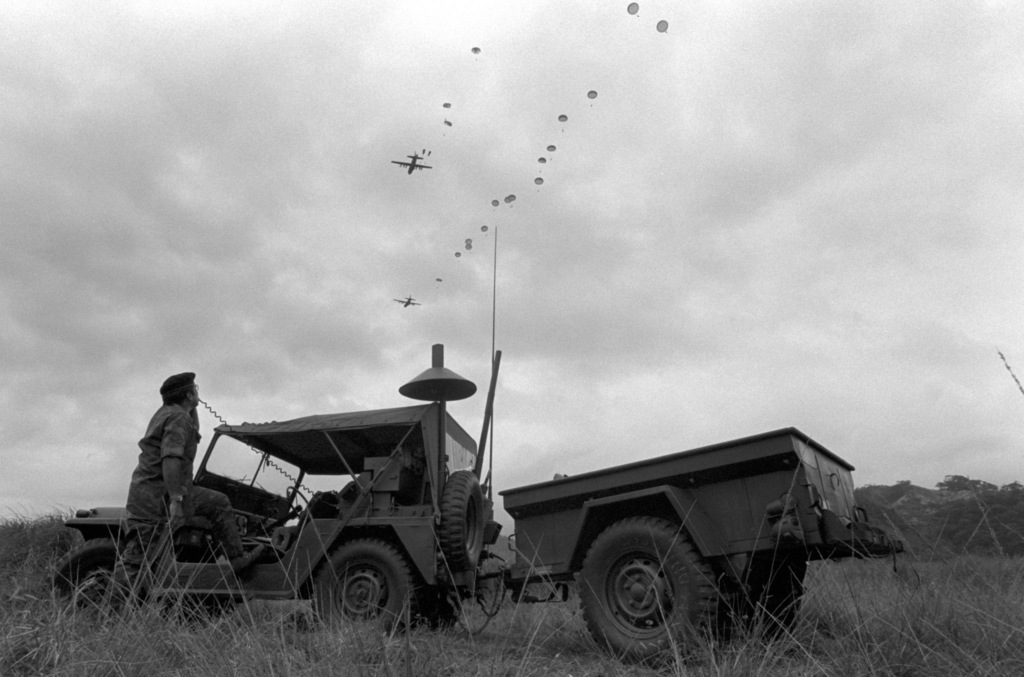U.S. Air Force combat controller, TSGT Ernest C. Gomez of the 1300th Military Airlift Squadron, monitors a C-130 Hercules aircraft parachute drop made by members of the U.S. Army 193rd Infantry Brigade during an airborne training mission at Venado Drop Zone