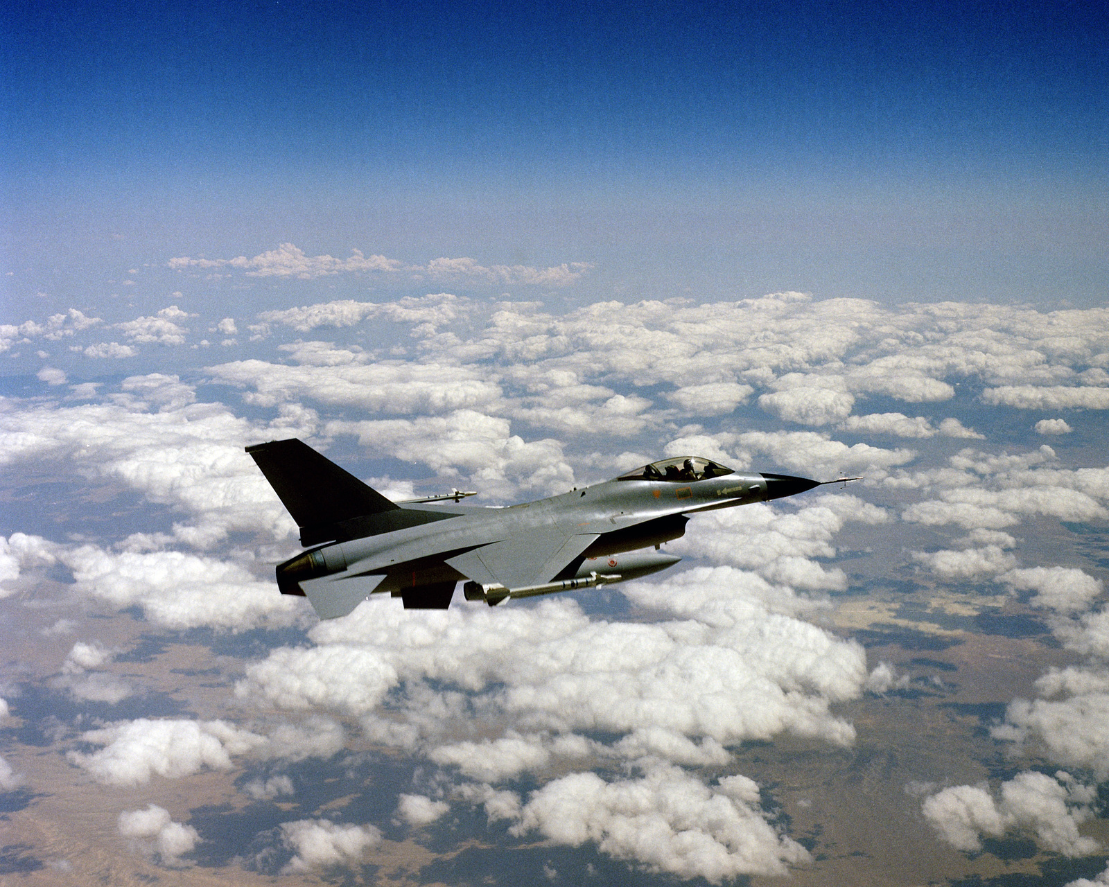 An air to air right side view of a YF-16 Fighting Falcon aircraft armed with AIM-9 Sidewinder missiles on the wing tips