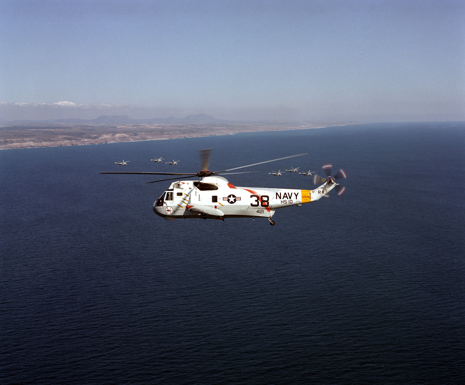 An air-to-air left side view of a Helicopter Anti-submarine Squadron 10 (HS-10) SH-3D Sea King helicopter as it operates off the coast of Southern California. Six other Sea King helicopters are in the background