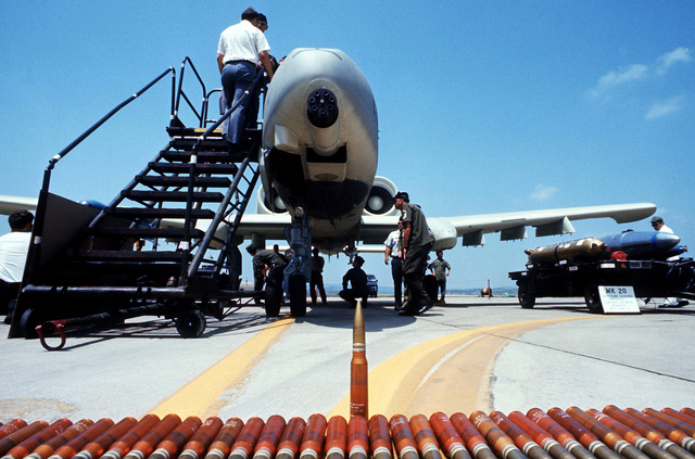 A front view of an A-10 Thunderbolt II aircraft on static display during a tour of air bases on Korea to familiarize Korean and American field commanders with its capabilities. In the foreground are 30 mm shells for the seven-barrel cannon on the A-10. On the right is an example of the Mark 20 Rock Eye cluster bomb that can be carried by the A-10