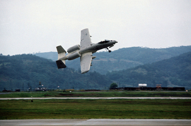 A ground-to-air view of an A-10 Thunderbolt II aircraft taking off during a demonstration tour of air bases in Korea to familiarize Korean and American field commanders with its capabilities