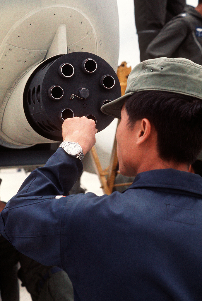 A Korean airman examines the General Electric GAU-8/A Avenger 30mm seven-barrel cannon mounted on an A-10 Thunderbolt II aircraft. The A-10 is on a demonstration of air bases in Korea to familiarize field commanders with its capabilities