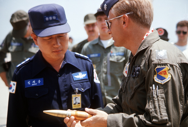 A member of the crew of an A-10 Thunderbolt II aircraft presents a dummy cannon shell from the General Electric GAU-8/A Avenger 30mm cannon on the A-10 to the commander of an air base in Korea. A shell was presented to the commander of each base visited by the A-10 crew during the tour to familiarize field commanders with the capabilities of the aircraft
