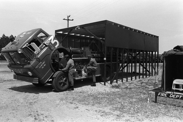 """A1C Parker Floyd and TSGT Richard Turner perform routine maintenance on a P-12 pumper at the Solid Shield fire station. Next to the wooden """"barn"""" used to house the fire truck is the tent where the firemen sleep during joint services exercise Solid Shield '77"""