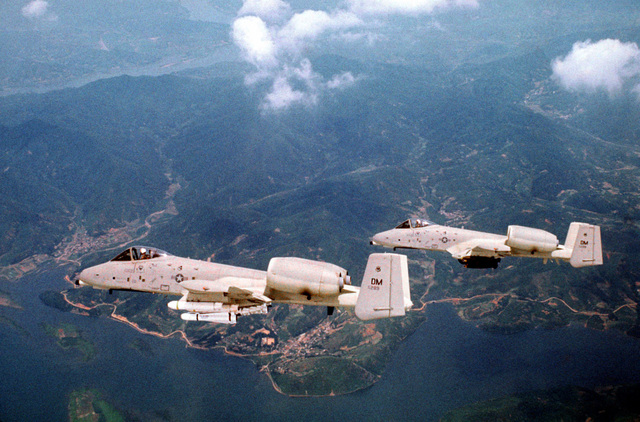 An air-to-air left side view of two A-10 Thunderbolt II aircraft. The A-10 in the background is carrying a full load of Mark 82 Snake Eye bombs. The A-10 in the foreground is loaded with two Maverick missiles and eight Mark 20 MOD-3 Rock Eye bombs. Both aircraft, assigned to the 355th Tactical Fighter Wing, are on a tour of Korean air bases