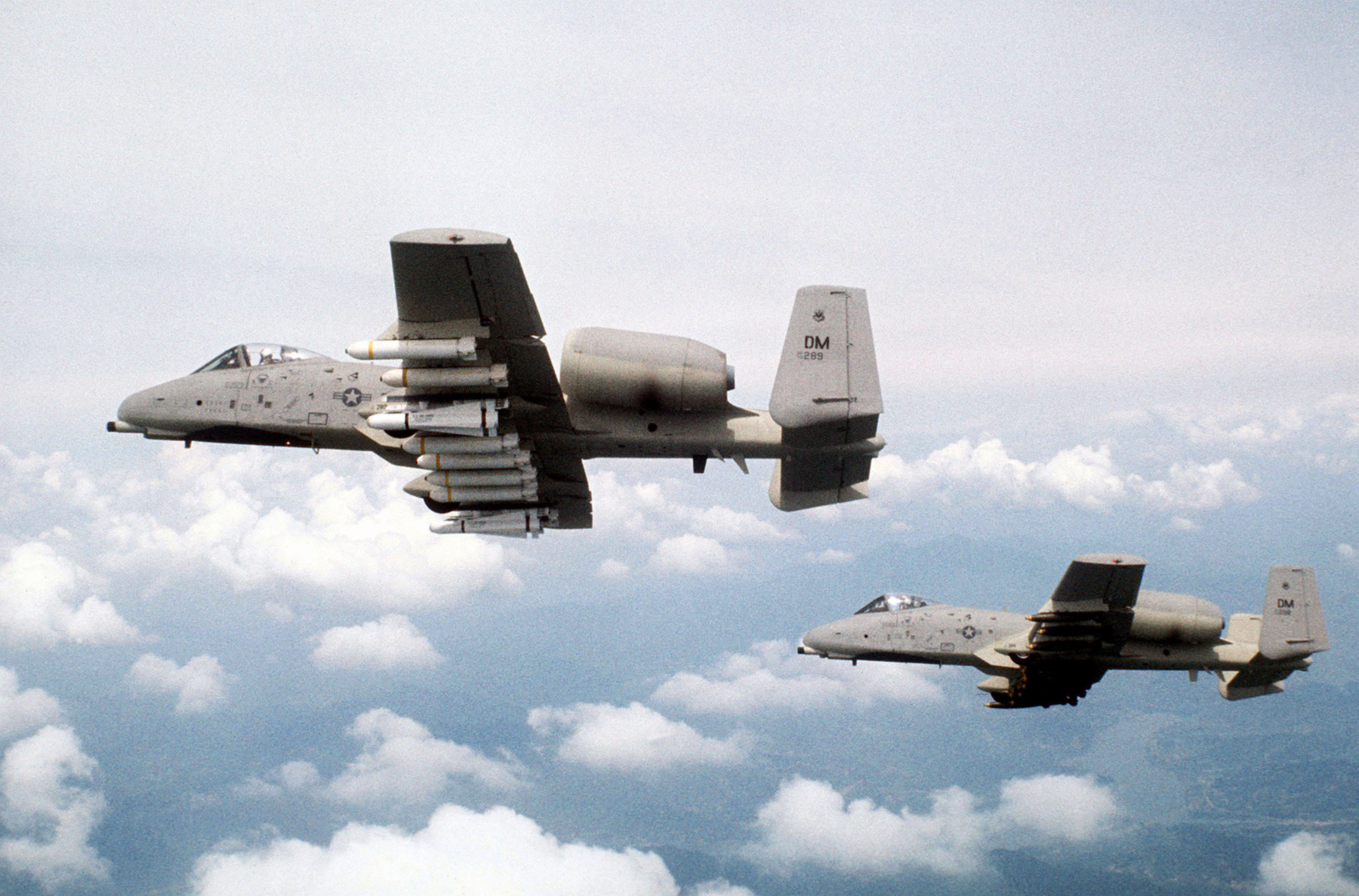 An air-to-air left underside view of two A-10 Thunderbolt II aircraft. The A-10 in the background is carrying a full load of Mark 82 Snake Eye bombs. The A-10 in the foreground is loaded with two Maverick missiles and eight Mark 20 MOD-3 Rock Eye bombs. Both aircraft, assigned to the 355th Tactical Fighter Wing, are on a tour of Korean air bases