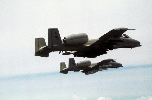 An air-to-air right underside view of two A-10 Thunderbolt II aircraft. The A-10 in the foreground is carrying a full load of Mark 82 Snake Eye bombs. The A-10 in the background is loaded with two Maverick missiles and eight Mark 20 MOD-3 Rock Eye bombs. Both aircraft, assigned to the 355th Tactical Fighter Wing, are on a tour of Korean air bases