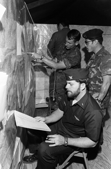 LTJG Hugh O'Doherty, a Coast Guard helicopter pilot, plots an air support operation in the Tactical Air Control Center during joint services exercise Solid Shield '77. Assisting him are CPT Kenneth LaPlante and MSGT Feliciano Guzman, both of the Army's Special Forces