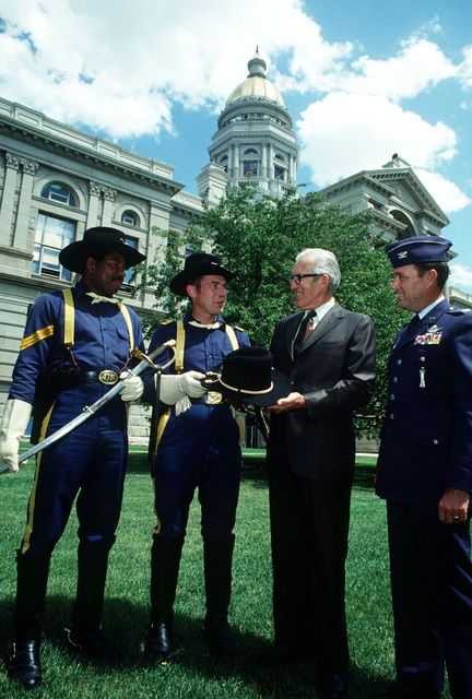 Major David Vaughn and STAFF Sergeant Jay B. Brown (wearing 5th Cavalry uniforms) present a hat and saber to Governor Ed Herschler of Wyoming, as Colonel James M. Cowan, Strategic Missile Wing commander, looks on