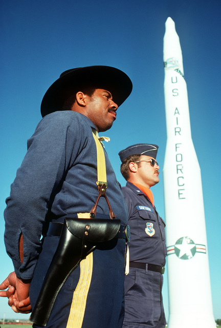 """STAFF Sergeant John Brown (in cavalry uniform) and missile launch officer Richard C. Soetaret pose in front of a Minuteman missile replica outside the main gate, to represent the """"muskets to missiles"""" theme of the 5th Cavalry reorganized"""