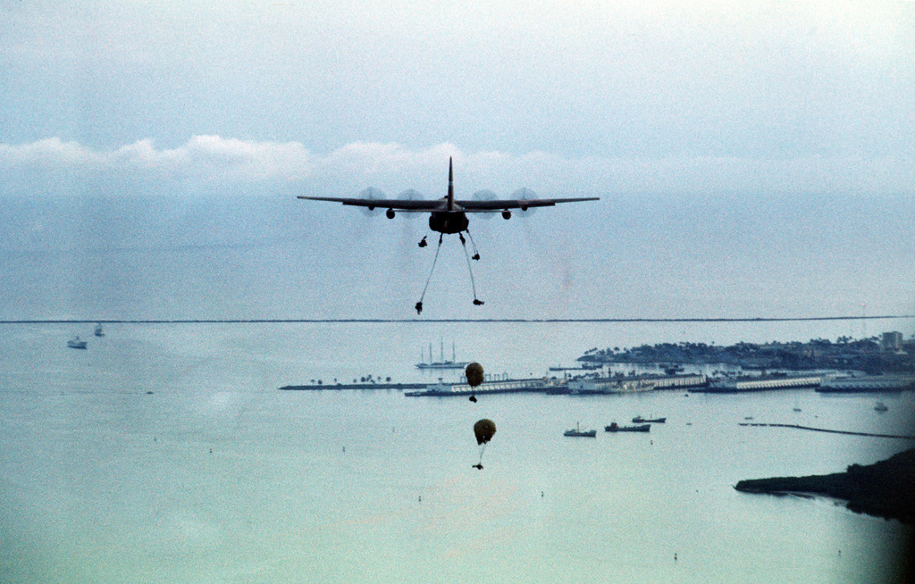 US Army paratroopers from Company A, 3rd Battalion, 5th Infantry, are air-dropped over the Gatun drop zone by a C-130 Hercules aircraft. Air Force units are assisting troops participating in an Army Training and Evaluation Program (ARTEP)