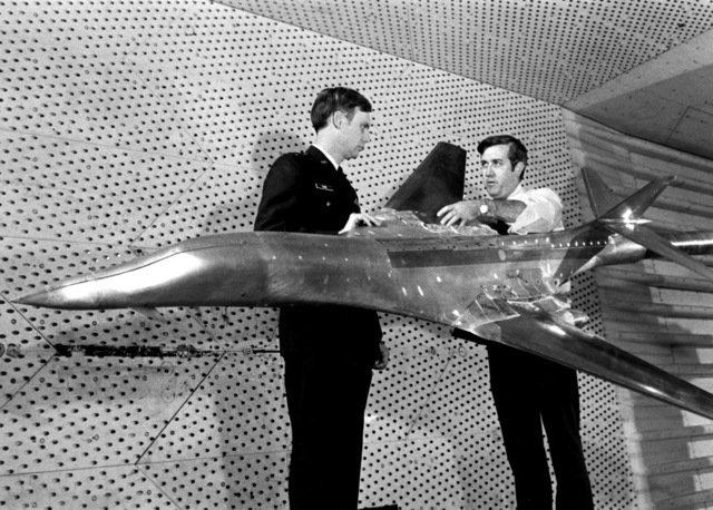 CAPT. Bill Tuck Jr., left, and Frank Keeny, ARO project engineer, examine a B-1 bomber model undergoing transonic wind tunnel testing at the Arnold Engineering Development Center. The tests are being conducted to examine the ability of various fairings to improve the quality of the airflow over the aircraft`s wing where it joins the fuselage