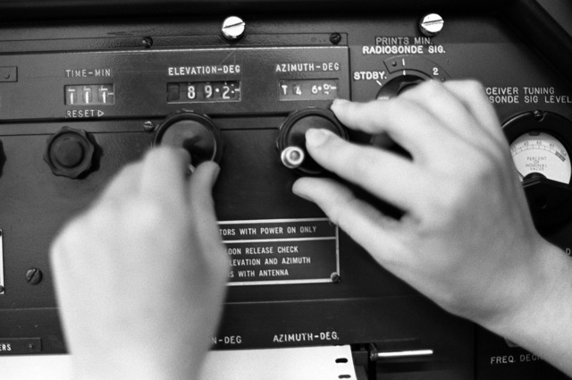 A technician adjusts the console controls of the control record for a ground meteorological detection antenna