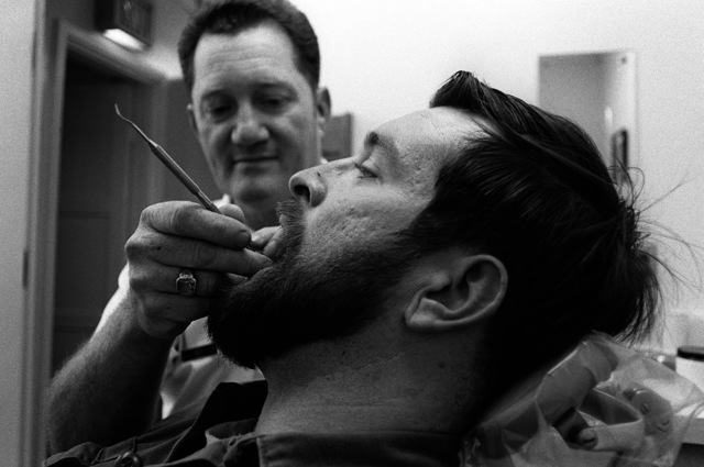 SSGT Ernest Witt, a hygienist at the main base dental clinic, cleans the teeth of PO3 George Pollard