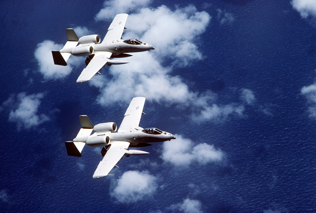 An air-to-air right topside view of two A-10 Thunderbolt II aircraft in close formation