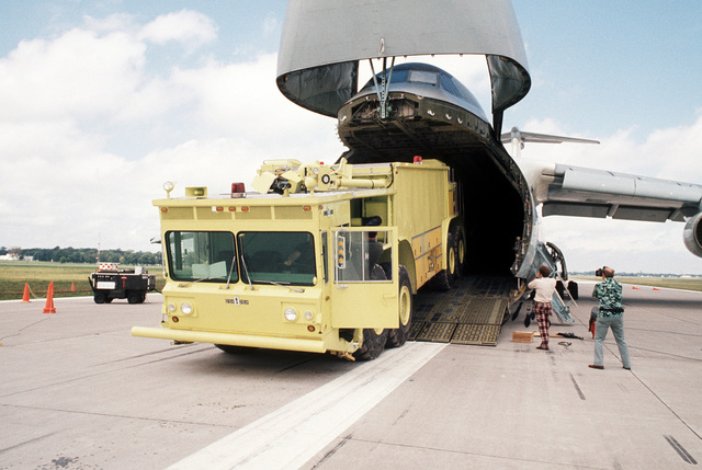 A prototype of the U.S. Air Force P-15 fire truck is backed into the front loading ramp of a C-5 Galaxy aircraft from the Military Airlift Command. The fire truck is being tested to see if it can be airlifted by the C-5