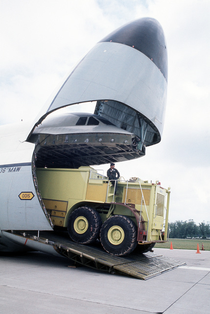 A prototype of the U.S. Air Force P-15 fire truck is driven up the front loading ramp of a C-5 Galaxy aircraft from the Military Airlift Command. The fire truck is being tested to see if it can be airlifted by the C-5