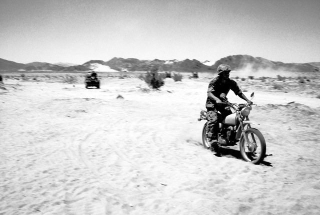A Marine motorcycle scout leads a jeep patrol across the Mojave Desert during Exercise BRAVE SHIELD XVI
