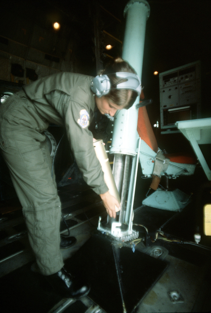 SGT. Debbie Whitacre, 54th Weather Reconnaissance Squadron, prepares to launch a dropsonde sensor from a WC-130 Hercules aircraft to measure a typhoon's speed and direction. The information will be relayed to the Joint Typhoon Warning Center (JTWC)
