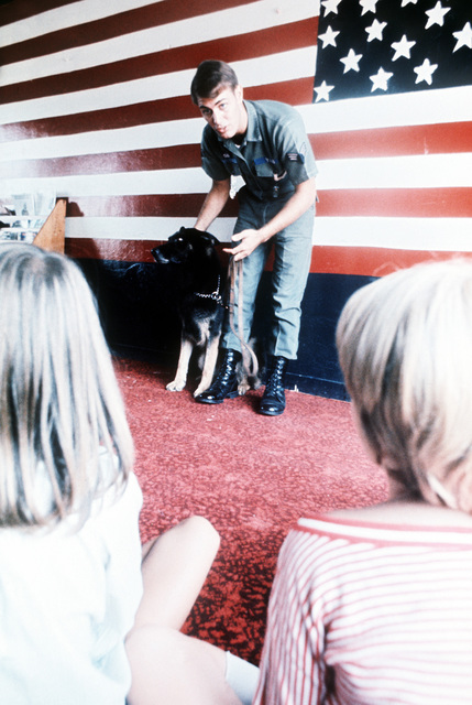 SRA Kevin Day, winner of the Outstanding AIRMAN of the Year award, demonstrates his skills as a dog handler to a group of children from a summer camp