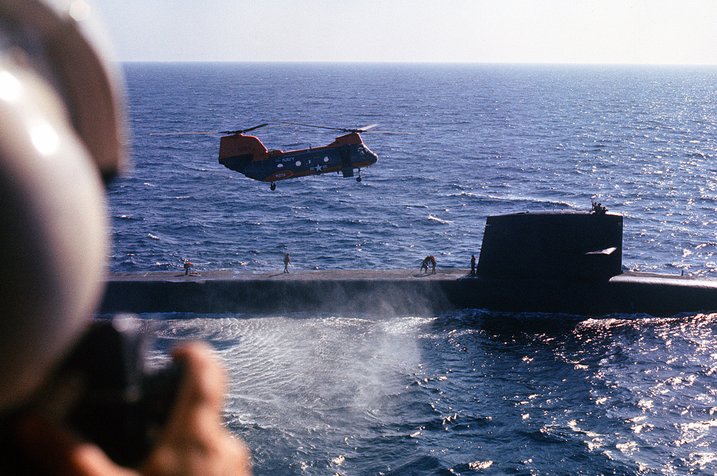 An HH-46A Sea Knight helicopter hovers over the nuclear-powered ballistic missile submarine USS GEORGE WASHINGTON CARVER (SSBN-656)