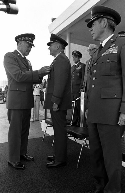 General Russell E. Dougherty receives the Defense Distinguished Service Medal from GEN Geroge S. Brown, chairman of the Joint Chiefs of STAFF, during his change of command and retirement ceremony. GEN Richard H. Ellis, his successor as commander in chief of the Strategic Air command, looks on