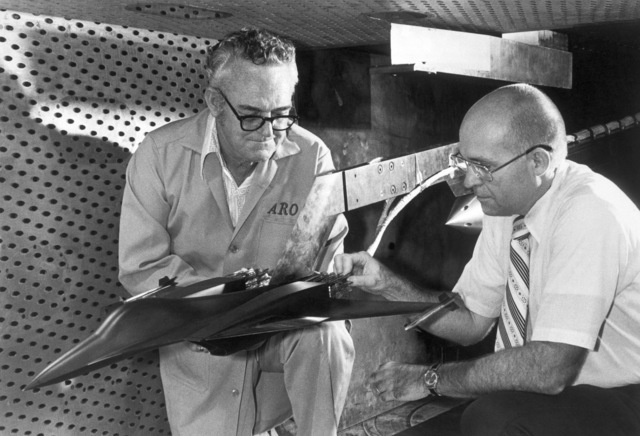 Jack Walker, a General Dynamics engineer, right, and Al Brooks, a test facility craftsman for ARO Inc., examine an advanced design concept of a fighter aircraft in the four-foot transonic wind tunnel at the Arnold Engineering Development Center