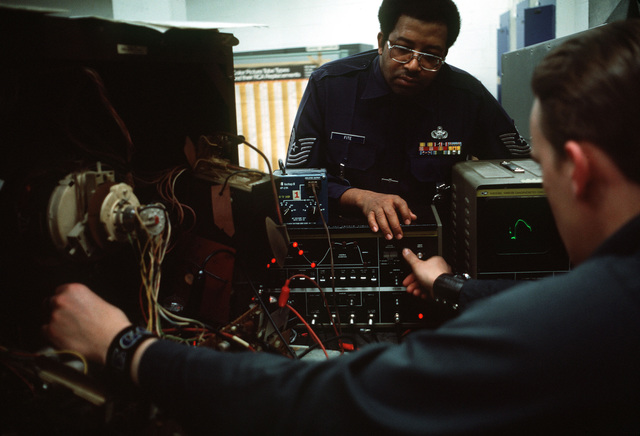 MASTER Sergeant Leonard Fite hrlps an inmate study electronics at the US Disciplinary Barracks
