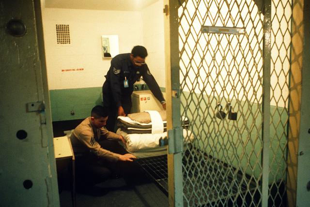 STAFF SGT. Robert White and Marine SGT. Bill Medina inspect a 6-foot cell at the U.S. Disciplinary Barracks