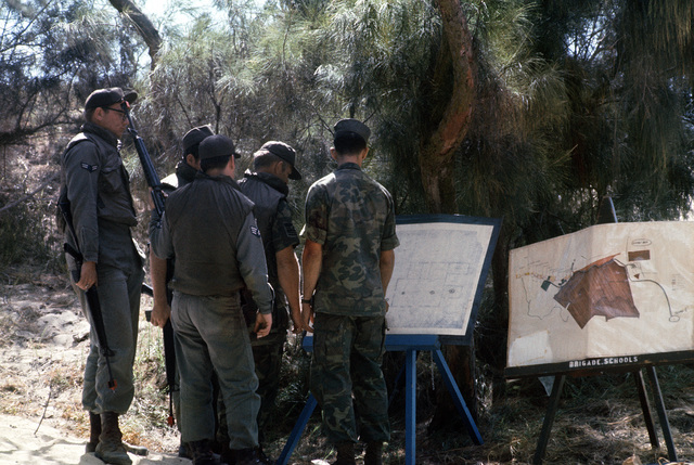 A group of Air Force security policemen gather around SSGT Richard Bishop, a Marine Corps instructor, as he briefs them on the details of an anti-terrorist operation. The policemen are participating in an anti-terrorist exercise being conducted by the 1ST Marine Brigade School