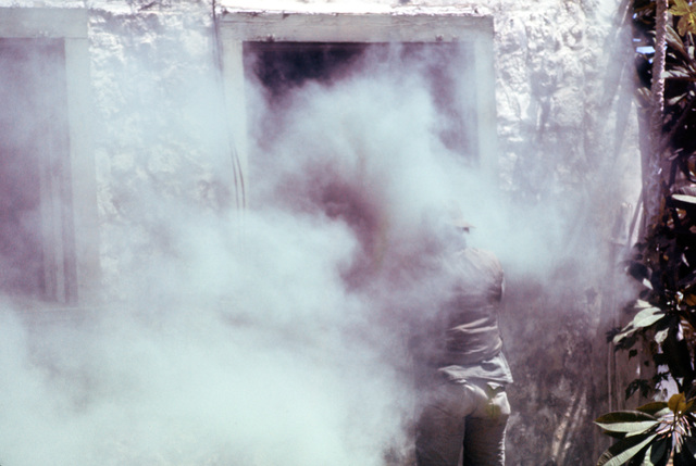 """An Air Force security policeman prepares to enter a smoke-filled building being occupied by """"terrorists."""" He is with a group of security police who are participating in anti-terrorist training being conducted by the 1ST Marine Brigade School"""
