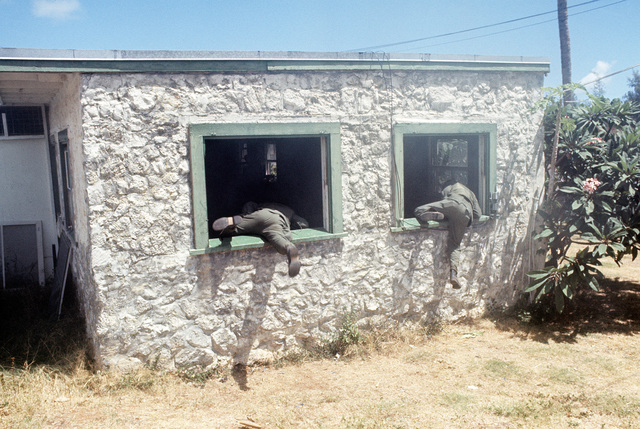 "Two Air Force security policemen climb through the windows of a ""terrorist-held"" building during a mock attack on the position. They are participating in anti-terrorist training being conducted by the 1ST Marine Brigade School"