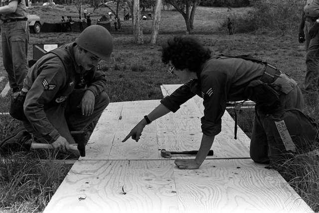 SGT Allen and SRA Ella Kirkham construct a latrine shelter during an exercise. They are part of the Base Engineering Emergency Force, Prime Beef