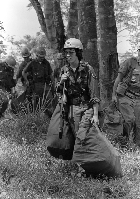 SRA Ella Kirkham carries a duffle bag, mobility bag and M-16 rifle toward her campsite. Kirkham is part of the Base Engineering Emergency Force, Prime Beef