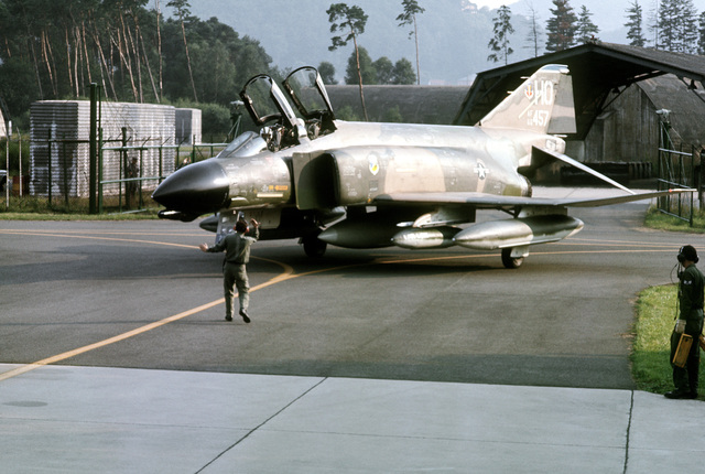 A plane director guides an F-4 Phantom II aircraft from the 8th Tactical Fighter Squadron to a parking spot. The F-4 has just arrived at the base to participate in exercise Crested Cap '77