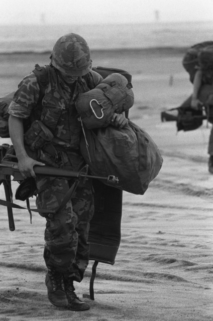 A paratrooper from the 82nd Airborne Division gathers his equipment after a drop at the Sicily drop zone during Exercise NEPTUNE II