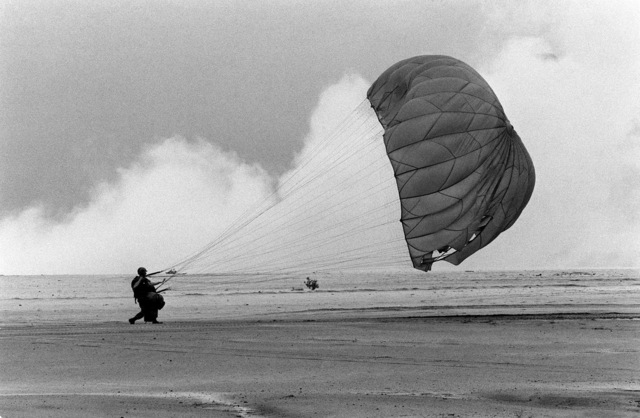 A paratrooper from the 82nd Airborne Division lands at the Sicily drop zone during Exercise NEPTUNE II