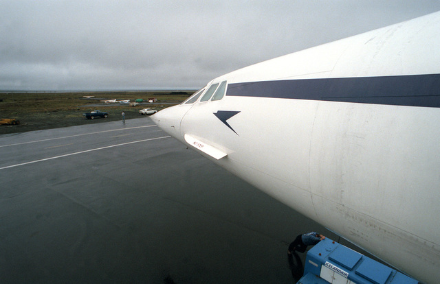 A view from the top of the boarding ladder of the nose of a British Airways Concorde aircraft parked on the flight line.  The aircraft is on an around-the-world test flight