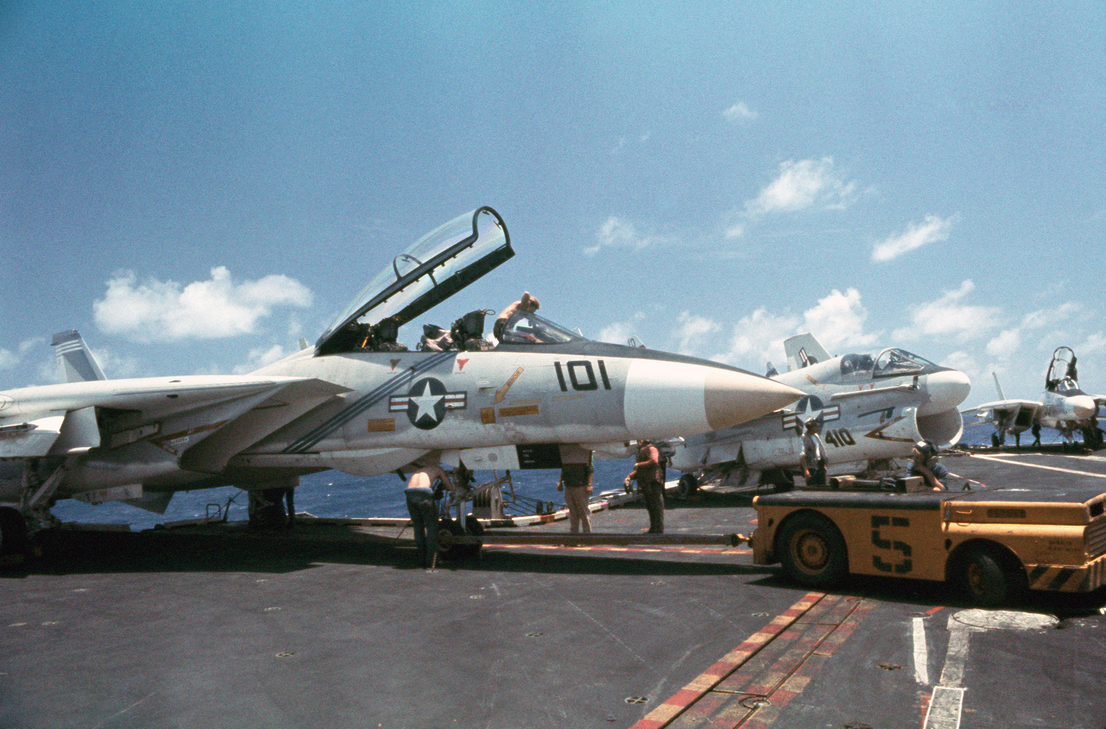 An MD-3A tow tractor stands by to maneuver an F-14A Tomcat aircraft on the flight deck of the aircraft carrier USS AMERICA (CV 66)