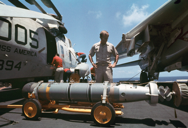 An ordnance officer inspects a Mark 46 torpedo on an Aero 21A weapons skid being loaded aboard an SH-3 Sea King helicopter parked on the flight deck of the aircraft carrier USS AMERICA (CV 66)