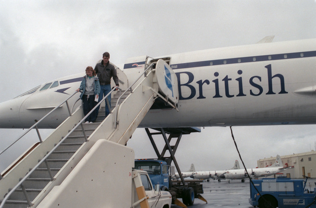 Two passengers exit a British Airways Concorde aircraft parked on the flight line.  The aircraft is on an around-the-world test flight