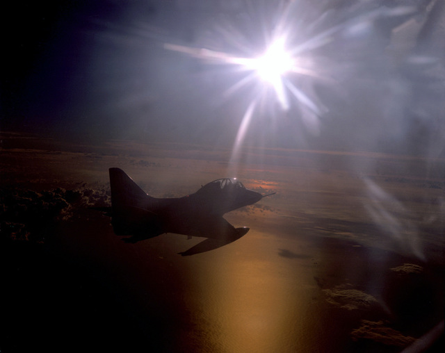 A right rear view of a TA-4J Skyhawk aircraft from Fleet Composite Squadron 1 (VC-1) flying in the direction of a bright setting sun