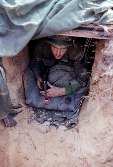 AIRMAN First Class Kenneth W. Hebert of the 58th Security Police Squadron, Luke Air Force Base, Arizona, stands guard in a foxhole during Exercise BOLD EAGLE '78. His unit is securing the perimeter of a base for the 82nd Airborne Division