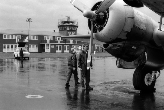 Flight line personnel perform a preflight check on a C-117 Skytrain aircraft parked on the flight line.  The aircraft is about to make its last flight